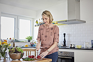 Mature woman preparing a salad in kitchen - RBF06070
