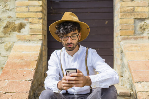 Man wearing old-fashioned clothes using cell phone - MGIF00139