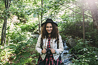 Portrait of smiling teenage girl with camera in nature - VPIF00100