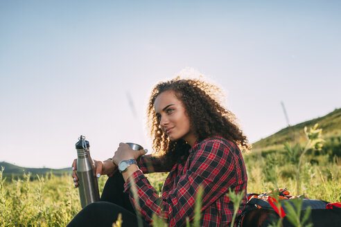 Teenage girl with thermos flask having a rest in nature - VPIF00106