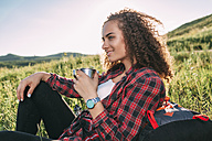 Teenage girl with thermos flask having a rest in nature - VPIF00109