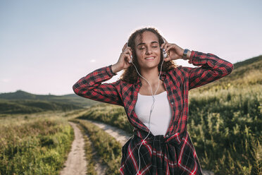 Teenage girl listening music with headphones in nature - VPIF00112
