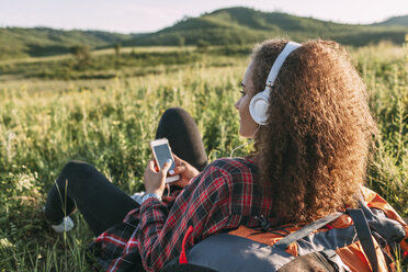 Teenage girl with backpack listening music with headphones on a meadow - VPIF00118