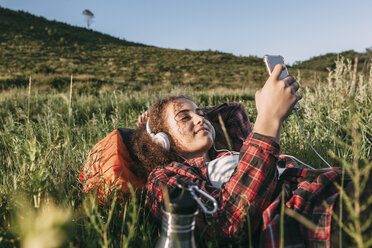 Teenage girl with backpack lying on a meadow listening music with headphones and cell phone - VPIF00121