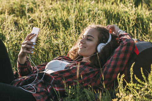 Teenage girl with backpack lying on a meadow listening music with headphones and cell phone - VPIF00124