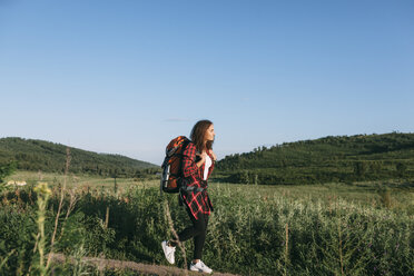 Teenage girl with backpack hiking in nature - VPIF00130