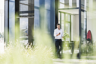 Businessman outside office building looking at cell phone - UUF11684