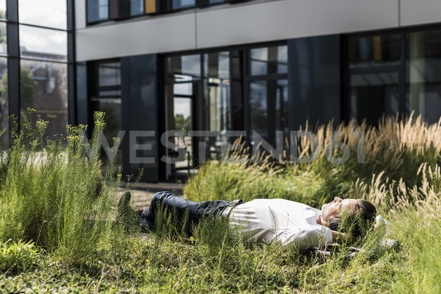 Businessman with headphones lying on a bench outside office building - UUF11687 - Uwe Umstätter/Westend61