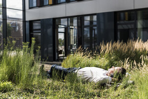 Businessman with headphones lying on a bench outside office building - UUF11687