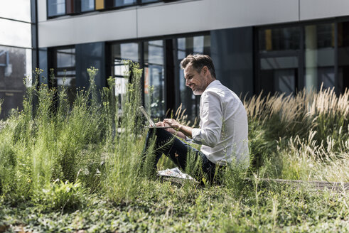 Smiling businessman working in grass outside office building - UUF11690