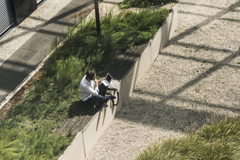 Businessman with headphones sitting on bench using tablet - UUF11693