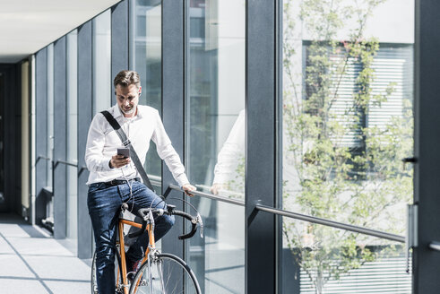 Businessman with cell phone on bicycle in office passageway - UUF11699
