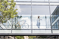 Businessman with bicycle in office passageway - UUF11702