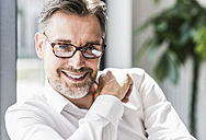 Portrait of smiling businessman with glasses - UUF11705