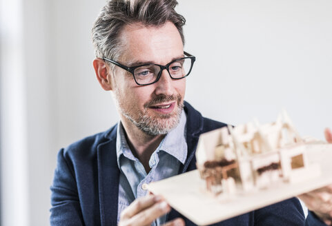 Architect looking at architectural model - UUF11720