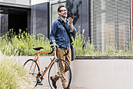 Smiling businessman with cell phone pushing bicycle - UUF11723