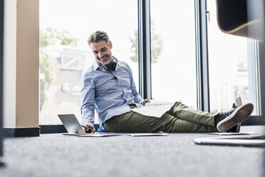 Smiling businessman working on the floor in office - UUF11732