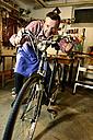 Senior man checking bicycle in his workshop - ECPF00130
