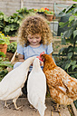 Little girl feeding chickens in allotment - NMSF00159