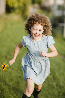 Happy little girl running on a meadow in the garden - NMSF00165