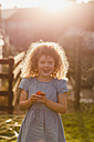 Portrait of little girl standing at backlight in the garden - NMSF00171