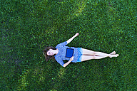 Young woman lying on grass, holding digital tablet - MAEF12416
