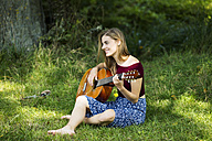 Young woman sitting on meadow, playing guitar - MAEF12425