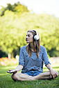 Young woman sitting in meadow, listening music with headphones - MAEF12431