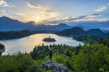 Slovenia, Bled,  Young woman taking picture of Bled island and Church of the Assumption of Maria at sunrise - LOMF00624