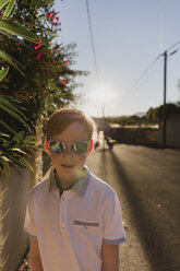 Portrait of boy wearing mirrored sunglasses at evening twilight - NMSF00177