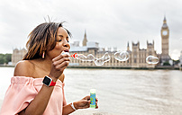 UK, London, woman making soap bubbles near Palace of Westminster - MGOF03630