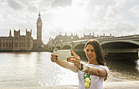 UK, London, beautiful woman taking a selfie near Westminster Bridge - MGOF03636