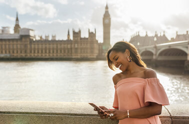 UK, London, woman sending messages with her smartphone near Westminster Bridge - MGOF03639