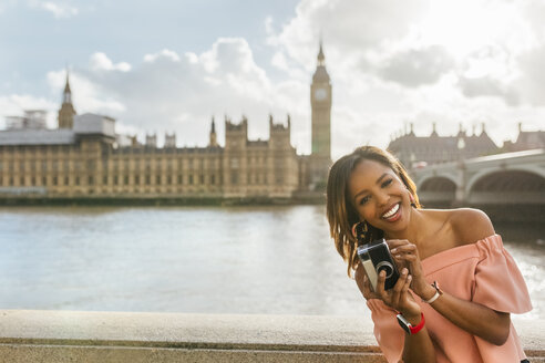 UK, London, happy woman holding a camera near Westminster Bridge - MGOF03645