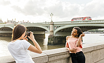 UK, London, woman taking a picture of her friend near Westminster Bridge - MGOF03648