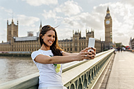 UK, London, beautiful woman taking a selfie on Westminster Bridge - MGOF03654