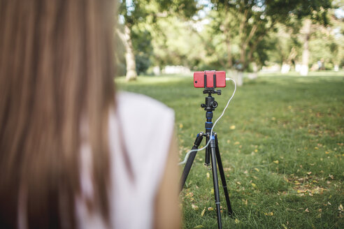 Woman working with camera phone on tripod on a meadow - VPIF00151