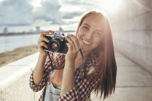 Smiling young woman with a camera at the riverside - VPIF00160