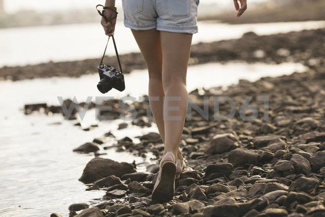 Woman holding a camera walking on stony beach - VPIF00169