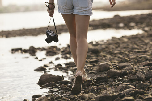 Woman holding a camera walking on stony beach - VPIF00169