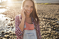 Portait of happy young woman on cell phone at the riverside - VPIF00172