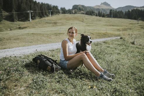 Austria, Vorarlberg, Mellau, woman with dog on a trip in the mountains - DWF00297