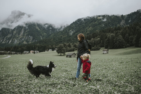 Austria, Vorarlberg, Mellau, mother and toddler with dog on a trip in the mountains - DWF00300
