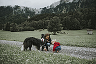 Austria, Vorarlberg, Mellau, mother and toddler with dog on a trip in the mountains - DWF00303