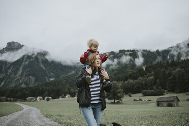 Austria, Vorarlberg, Mellau, mother carrying toddler on shoulders on a trip in the mountains - DWF00318