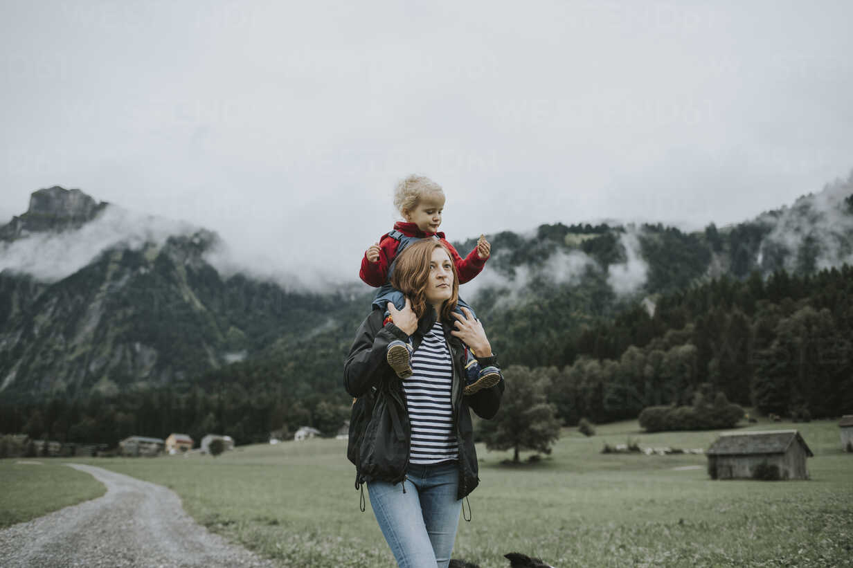 Austria, Vorarlberg, Mellau, mother carrying toddler on shoulders on a trip in the mountains - DWF00318 - Frederik Franz/Westend61