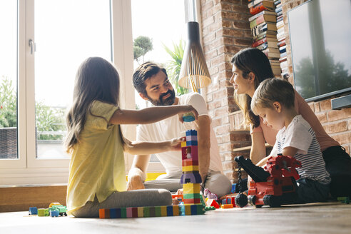 Family playing with building blocks on the floor together - JUBF00256