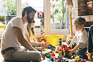 Family playing with building blocks on the floor together - JUBF00259