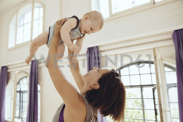 Sporty woman lifting up happy baby in training room - MFF03996