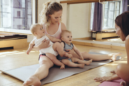 Mother with twin babies sitting on yoga mat - MFF03999